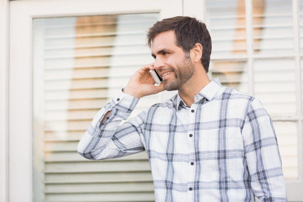 man smiling while talking to his phone