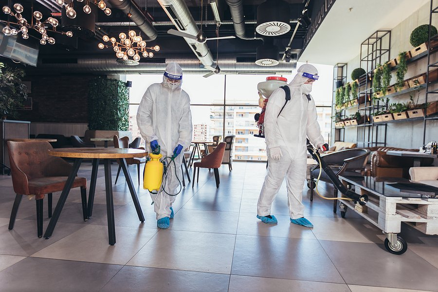 two people wearing protective suit is disinfecting the room
