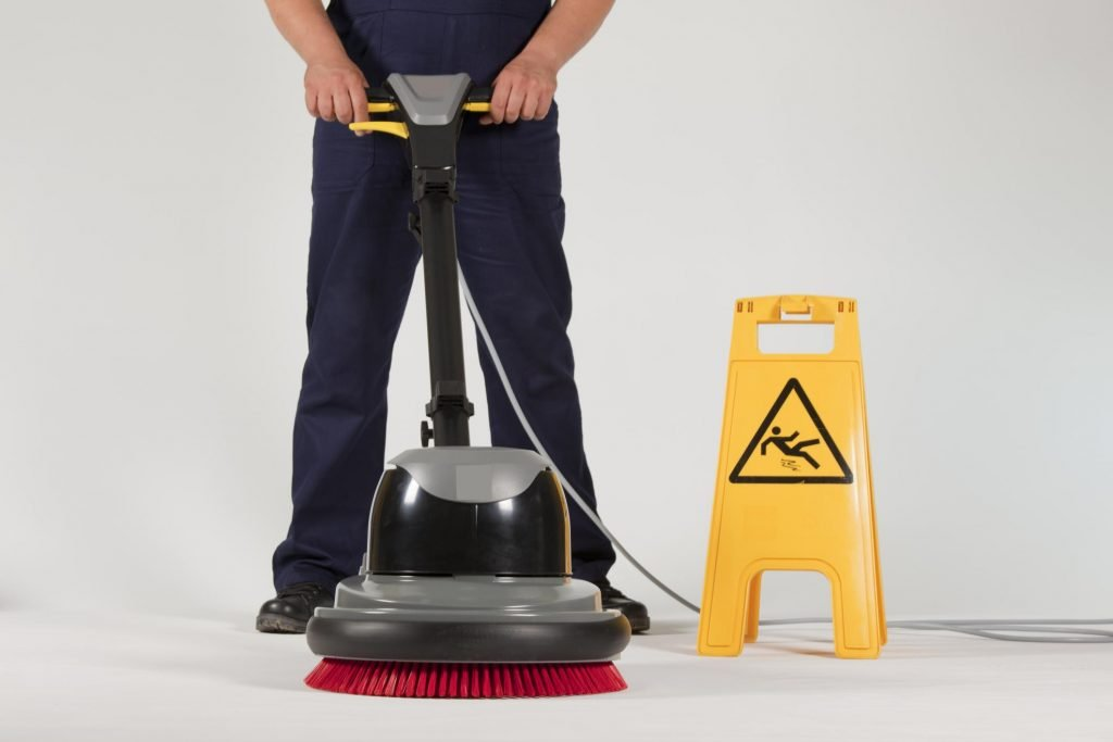 man cleaning the floor and have a wet sign
