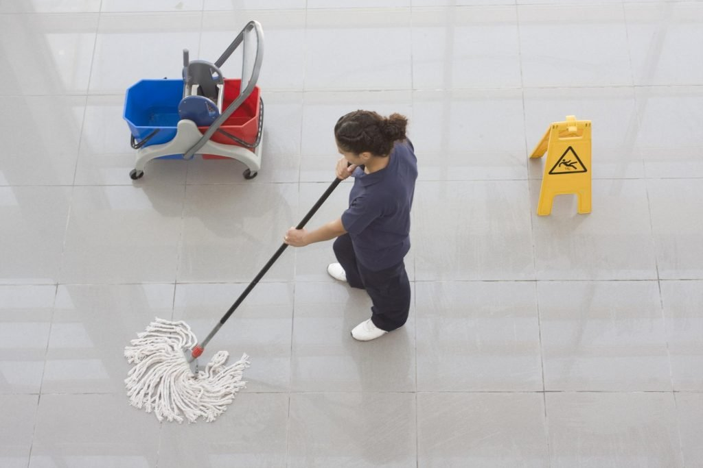 girl cleaning the floor using a mop