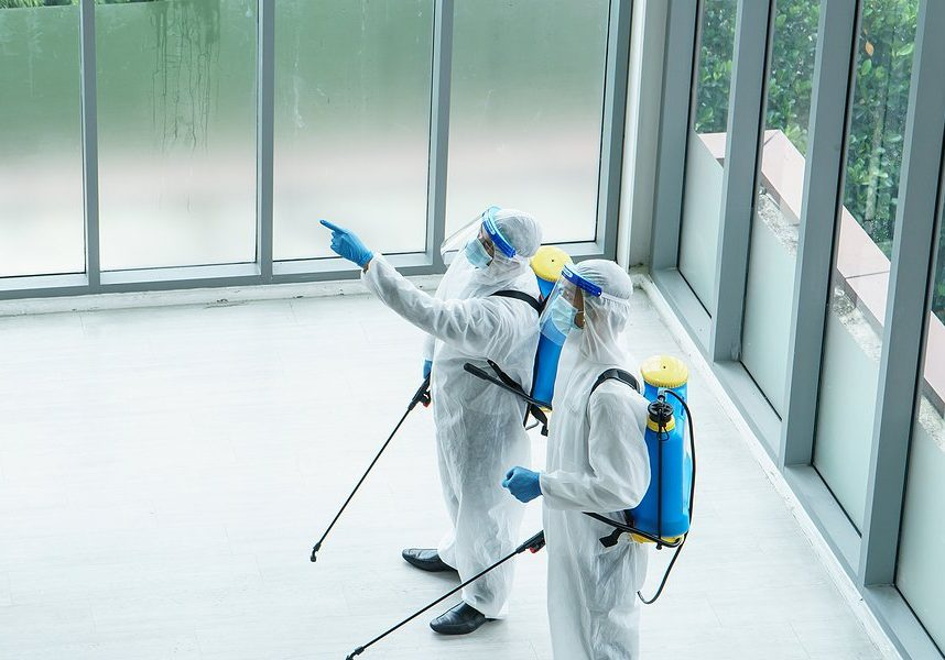 two people wearing protective suit while disinfecting